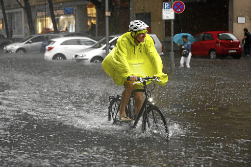 A cyclist rides on a flooded street during heavy rain in Berlin, Germany, on June 29 2017. Picture: REUTERS