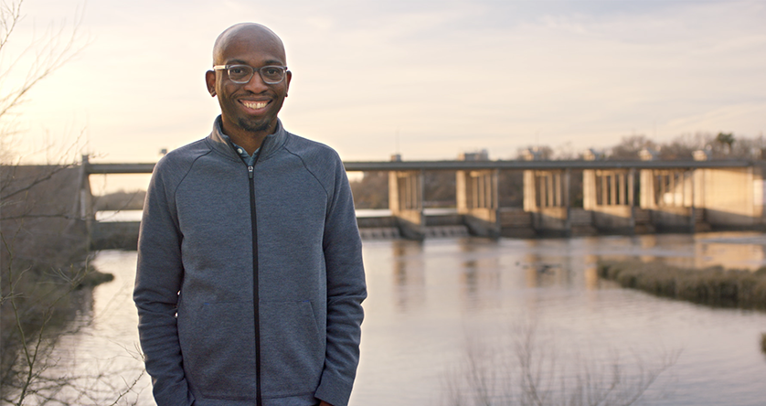 Founder Seyi Fabode smiles at the camera standing in front of a body of water in Texas.