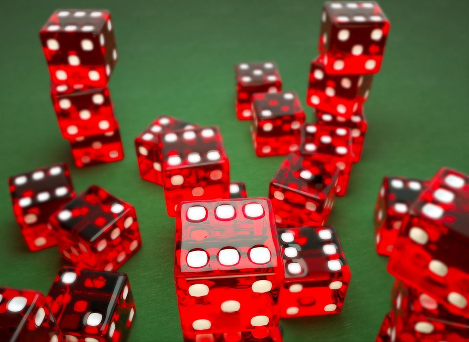 Lots of red dice are stacked on a green casino baize