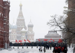 Photo: **CORRECTS TO LENIN'S MAUSOLEUM** Russian Communists hold red flags as they queue to lay flowers at the grave of Soviet dictator Josef Stalin to mark the 130th anniversary of his birth, as they walk along the Red Square in Moscow, Russia, Monday, Dec. 21, 2009. St Basil's Cathedral is seen at left and Lenin's mausoleum is at right.  (AP Photo/Alexander Zemlianichenko)