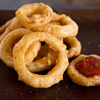 "Double Crunch, Beer-Battered Sweet Maui Onion Rings with a Spicy & Smoky, ""Kicked-Up Ketchup"" Dipping Sauce."