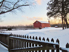Photo: Sunset and snow on an old wooden fence and red bar with windmill at Carriage Hill Metropark in Dayton, Ohio.