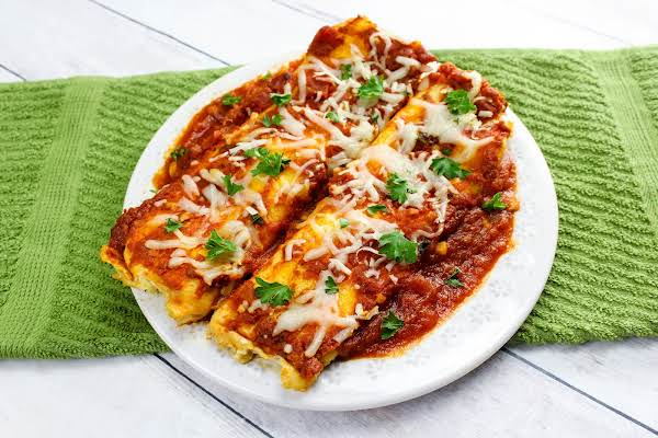 Two Pieces Of Homemade Manicotti On A Plate.