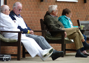 Photo: Umpire Victor and Organiser Frank chat. John Voice & Shirley Jones watch the game.