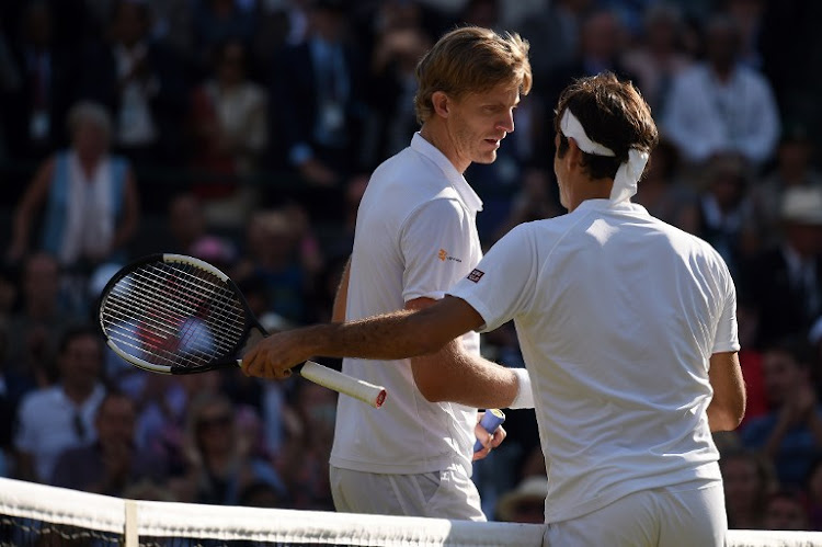 Switzerland's Roger Federer greets South Africa's Kevin Anderson after losing 2-6, 6-7, 7-5, 6-4, 13-11 in their men's singles quarter-finals match on the ninth day of the 2018 Wimbledon Championships at The All England Lawn Tennis Club in Wimbledon, southwest London, on July 11, 2018.
