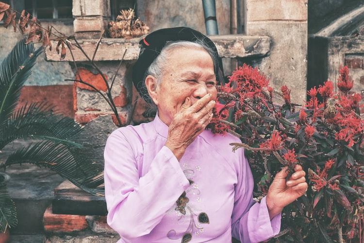 Uma senhora com a roupa roxa sorrindo