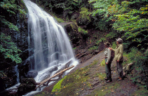 Hikers admire a waterfall in New Brunswick, Canada.