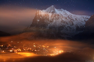 Photo: The nighttime lights of the town of Grindelwald shine in the fog, while Wetterhorn (3692m) towers above in the moonlight - December.