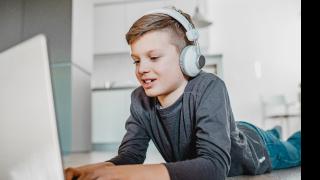 un niño con auriculares mirando un portátil