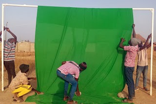 A small group of people put a green fabric on a wooden structure outside to create a green screen.