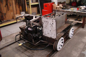 Photo: Front of CBL Chassis with the body removed, prior to steam cleaning.  Note sag on front upper frame sub-assembly. Also note ice cutting ridge on surface of front left wheel.