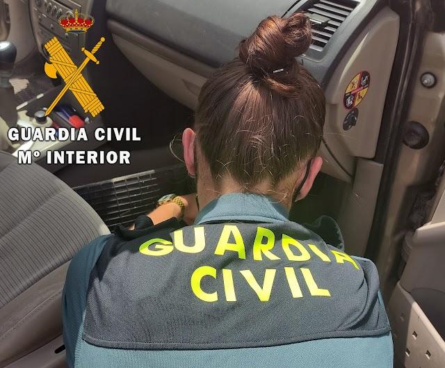 Una agente de la Guardia Civil inspecciona el coche.