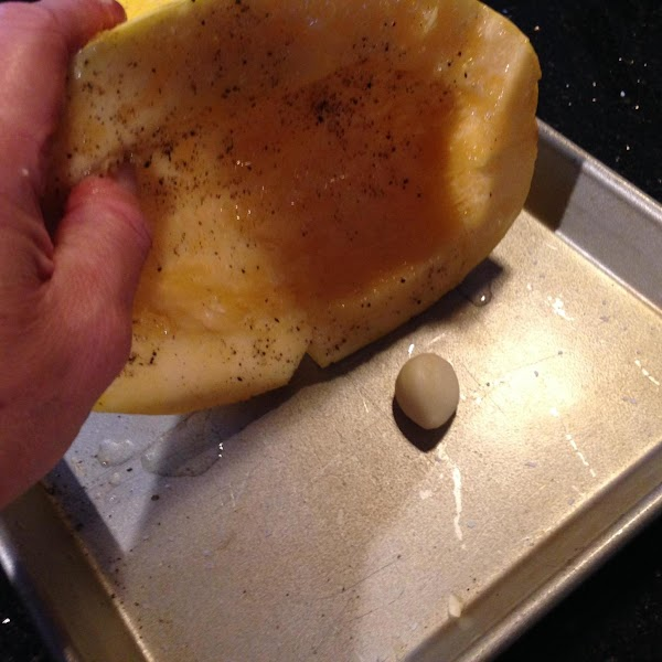 PLACE A CLOVE OF GARLIC ON A BAKING PAN N COVER WITH EACH HALF...