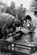 Photo: 13 Mar 1968, Hue, Vietnam --- Original caption: Communist Mine Wounds Children.  Hue, South Vietnam:  A medic of the 82nd Airborne binds the wounds of a Vietnamese girl injured when a group of children accidentally tripped a Viet Cong mine intended for U.S. vehicles.  The child's sister tries to comfort her.  A number of other children were also injured in the explosion two miles south of Hue. --- Image by © Bettmann/CORBIS