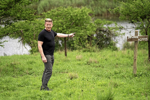 Gordon Ramsay points toward a sign warning about hippos.