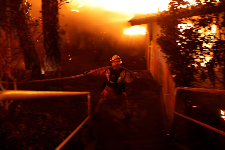 A firefighter drags a hose as he battles the Camp Fire in Paradise, California, US November 8, 2018.