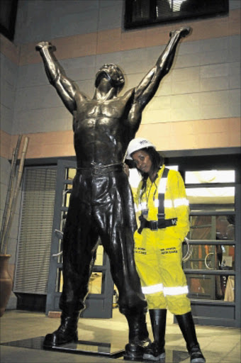 YOU GO GIRL: Third-year mining engineering student Mpeo Mahase stands next to the sculpture of the Unknown Miner at the University of the Witwatersrand. PHOTO: BAFANA MAHLANGU