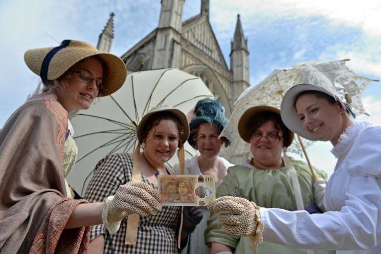 Jane Austen fans in period costume with the new note. Picture: REUTERS