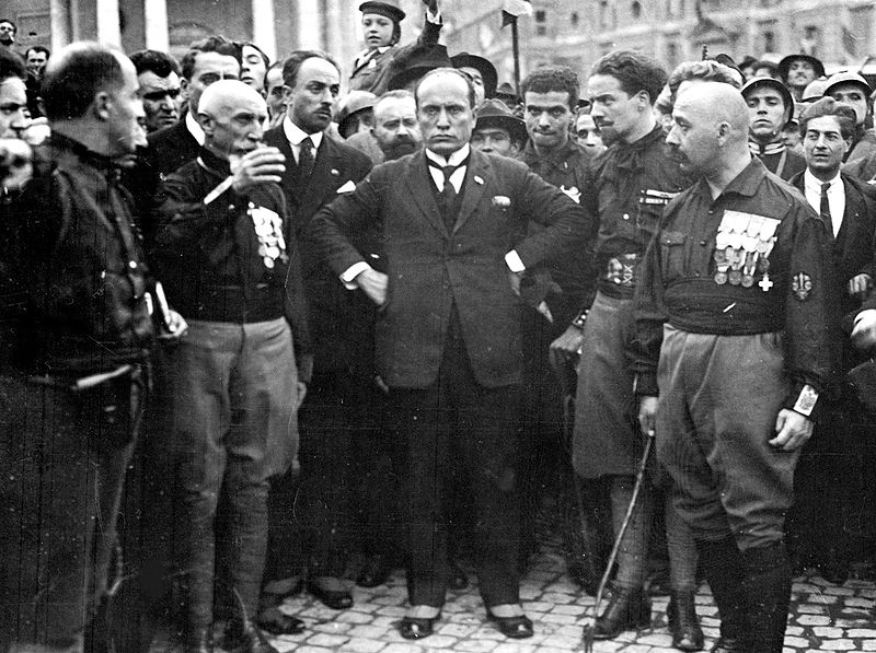 Mussolini standing in the midst of blackshirt Fascists.