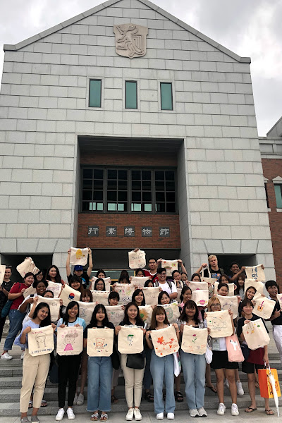 Students holding artwork outside a building while on Study Abroad Program in Daegu S.Korea