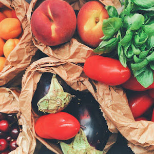 Overhead photo of fruit in paper bags, including stone fruit, cherries, eggplant, tomatoes, and spinach
