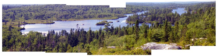 Photo: Cranberry Lake taken from a highpoint on The Bluff Trail south of the lake. The ensuing photos, taken Aug 5, 2014, begin at the north end of the lake, seen here in the distance. There are about a dozen islands in the southern 1/3rd of the lake. The shoreline has alternating stretches or patches of rocky granitic outcrops and wetlands, no sandy beaches! These photos highlight the rocky outcrops and large erratics.