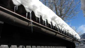 A roof with gutters cowered in snow.
