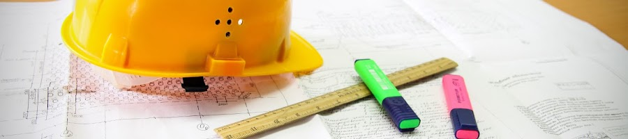 yellow safety helmet on building plans and a ruler
