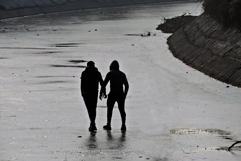 persone che si reggono nel canale ghiacciato di c