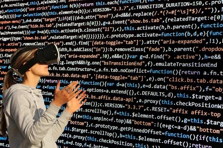 Frau mit Datenbrille vor Wand mit Computercode.