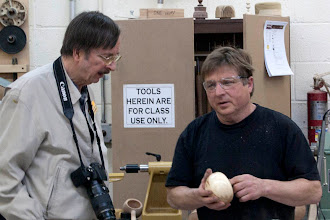 Photo: As Gary Guenther describes his hollow form, Mike does what every woodturner does first, feel the inside.