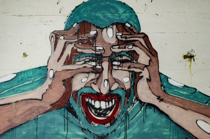 Painting of a man holding his head and looking stressed because chronic stress can hinder fat-loss over fifty.