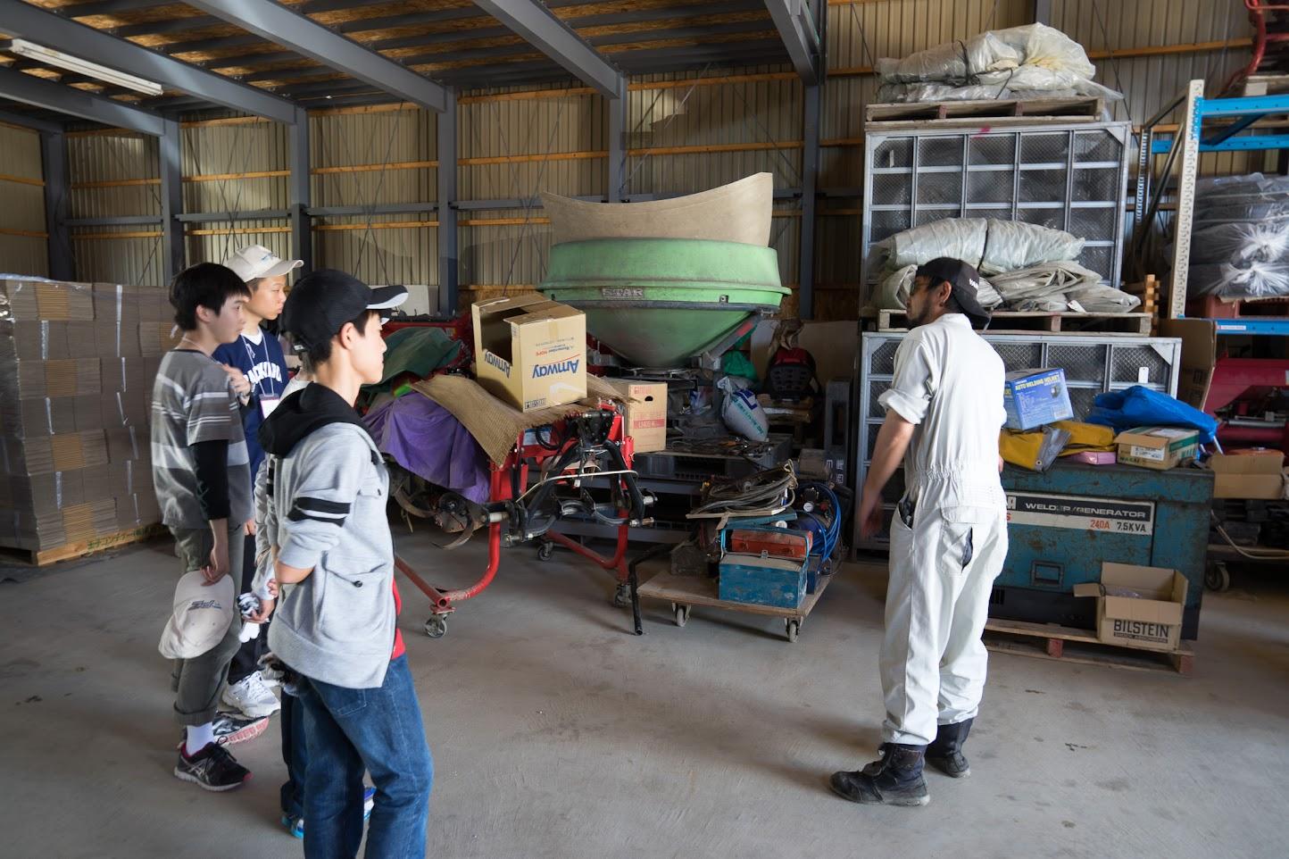 倉庫内の様々な農機具について説明
