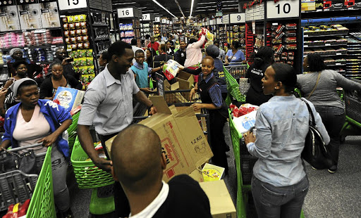 Shoppers jostle to buy products on special at the Mall of Africa in Midrand on Black Friday last year. The Black Friday shopping craze has taken South Africa by storm, with thousands of shoppers enduring long queues for massive discounts. / Felix Dlangamandla / Gallo Images
