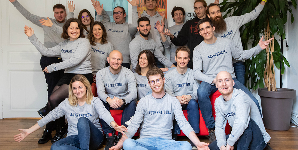 The Teester team is sitting for a group photo with matching grey sweaters.
