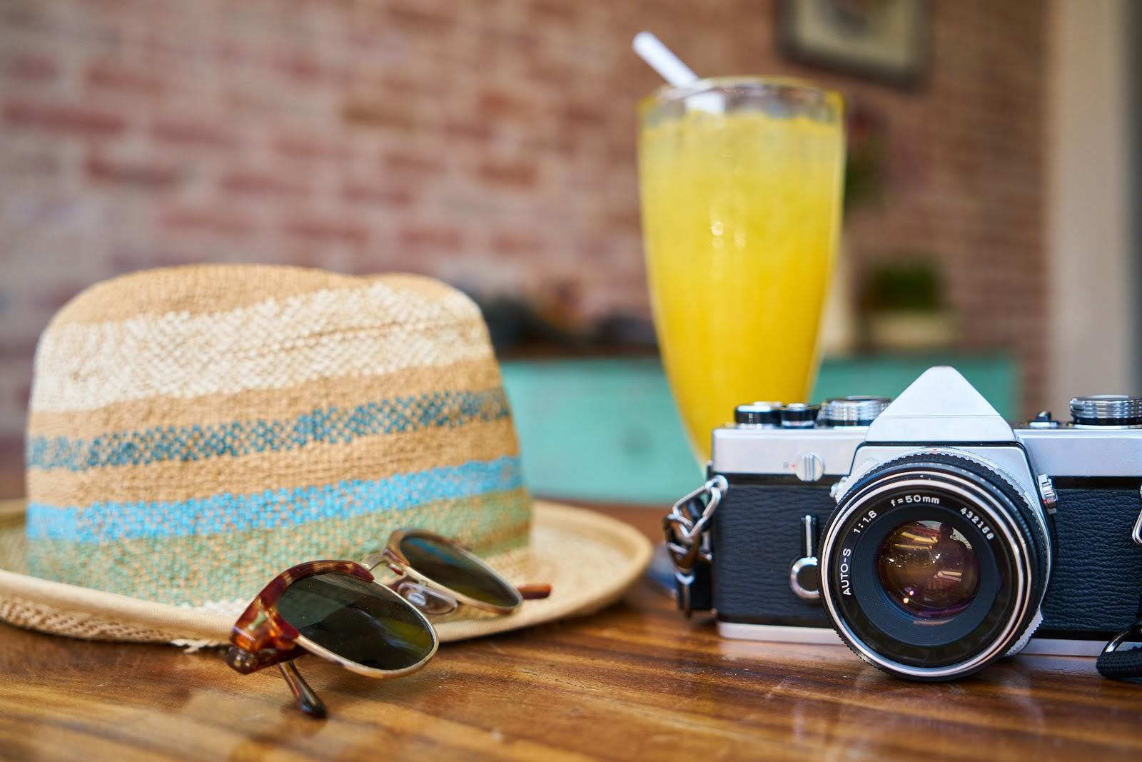 a camera, glasses, straw hat and orange juice on the table