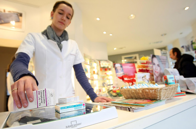 A pharmacist rings up antibiotic medication in a pharmacy. Fil ephoto