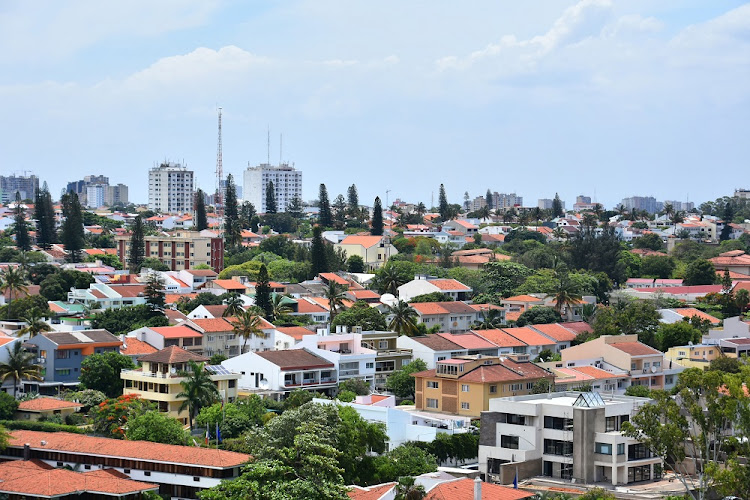 An elevated view of houses in a residential area in Maputo, the capital of Mozambique, with tall buildings in the background. Picture: 123RF/GREGORY MAASSEN