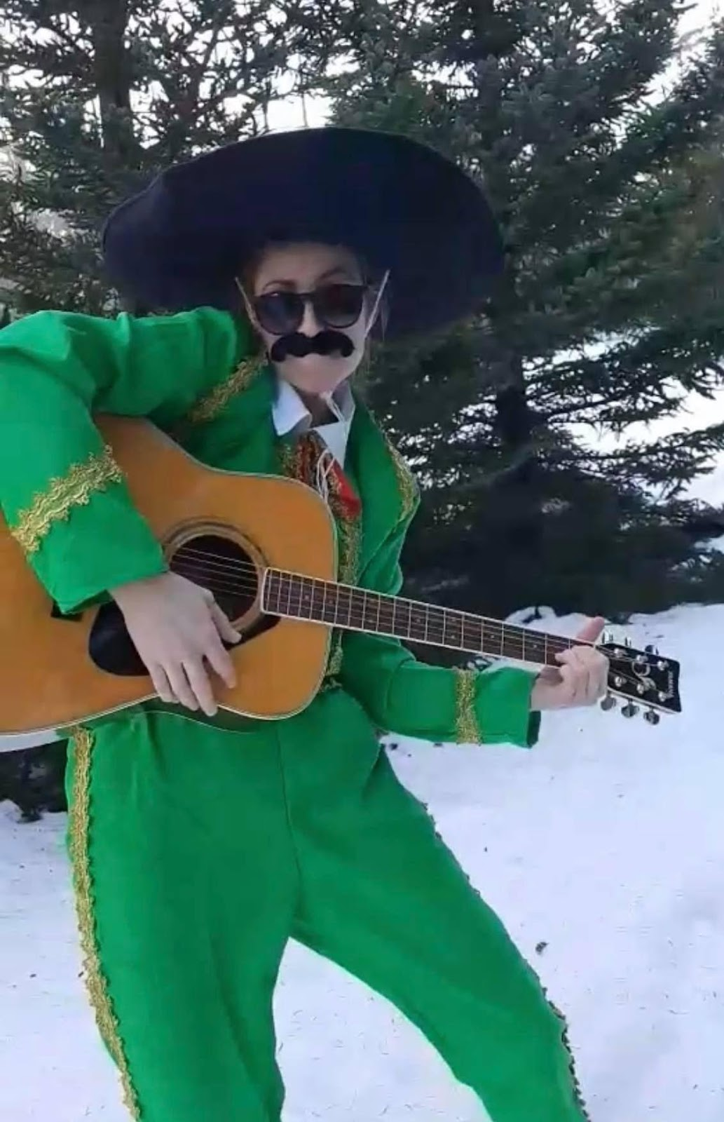 A person in a costume holding a guitar in the snow  Description automatically generated with medium confidence