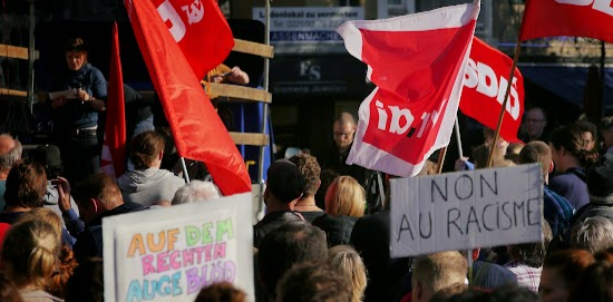 Demonstrantinnen mit Fahnen und Transparenten: »Auf dem rechten Auge blöd«, »Non au racisme«.
