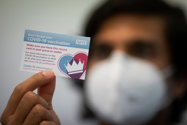 Staff member shows a vaccination reminder card as the Pfizer-BioNTech Covid-19 vaccine is administered at the Hurley Clinic in London, Britain. Picture: Aaron Chown/PA Wire/Pool via REUTERS