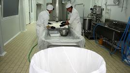 Un momento de la elaboración del queso, con el molde gigante en primer plano.