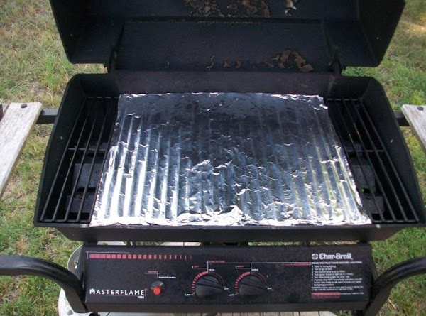 Place a sheet of aluminum foil on the grill grate and grease with vegetable...