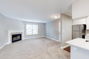 Open concept living and dining area with fireplace and access to the kitchen with white cabinets and stainless steel appliances