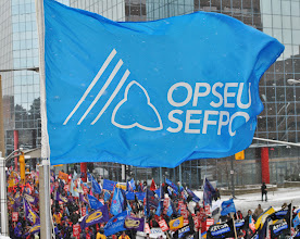 Photo: An Ontario Public Service Employees Union (OPSEU) flag hangs over the marching crowd below.