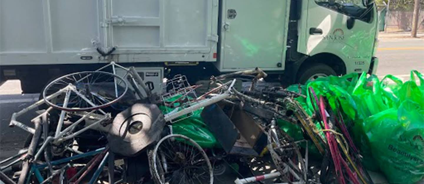 City of San Jose garbage truck with piles of broken bike parts and trash bags collected from the creek clean up.