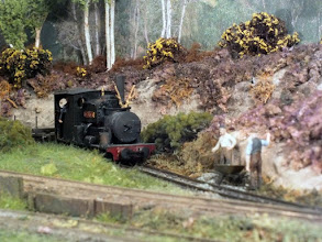 Photo: 013 Creech displays her antler smokebox decoration as she passes the PW gang at work shoring up the thinning ballast .