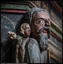 Photo: Eine Darstellung des Evangelisten Matthäus, der von einem Engel inspiriert, das Evangelium niederschreibt. Bäuerliche Schnitzerei in der Dorfkirche Mestlin. Der Flügel des Engels ist ein wenig ramponiert.