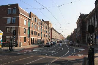 Photo: De Marnixstraat met links stadsvernieuwingsnieuwbouw uit de jaren '80 en '90. Rechts de sportwinkel Demmenie, voorheen katholieke jongensschool en verderop de door de partikulier Schutte in 1871 gebouwde blokken met 162 arbeiderswoningen