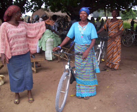 Photo: Elewy makes shea butter which she sells on market days in Heng, 8 miles round trip and in Ullo, 12 miles round trip from her home. Before she got this bike from Village Bicycle Project, she walked to the markets while carrying as much shea butter as she could.  With her bike, she will be able to travel faster, and carry more of her products to sell.  This will increase her income, save her precious time, and make life for her family better.